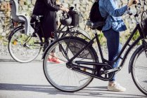 Faible proportion de femmes à bicyclette debout sur la route — Photo de stock