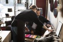 Задний вид молодой владелицы, показывающий тканевые образцы мужчине, сидящему на диване в магазине — стоковое фото