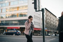 Smiling young woman talking on mobile phone walking against building in city — Stock Photo
