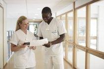 Счастливый мужского и женского медсестер, с использованием цифровых таблетки при рассмотрении документа в больничном коридоре — стоковое фото
