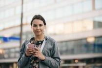 Портрет улыбающийся молодой женщины, стоя с мобильного телефона против строительства в городе — стоковое фото