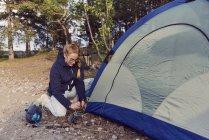 Joven mujer arrodillada mientras carpa camping - foto de stock