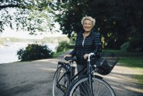 Portrait of smiling senior woman with bicycle in park — Stock Photo