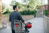 Vue arrière de l'homme marchant à vélo sur une passerelle en ville — Photo de stock