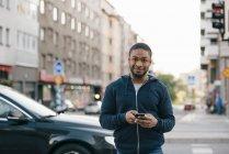 Портрет молодої людини, що стоїть за смарт-телефону в місті — стокове фото
