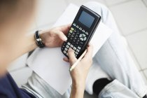 High angle view of male hands using calculator while — Stock Photo