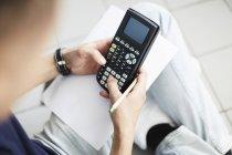 Высокий угол зрения мужских рук, с помощью калькулятора при — стоковое фото