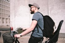 Vue latérale de l'homme portant un sac à dos en vélo sur la rue — Photo de stock