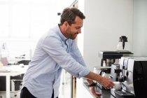 Empresario que utiliza cafetera en el mostrador de cocina de la oficina creativa. - foto de stock