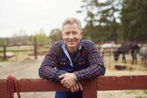 Портрет улыбающегося зрелого фермера, опирающегося на забор — стоковое фото