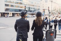 Vista posteriore dei colleghi di lavoro con biciclette in strada in città — Foto stock