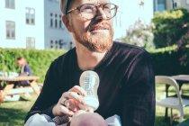 Homme adulte moyen regardant loin tout en nourrissant le lait du biberon au bébé garçon au parc — Photo de stock