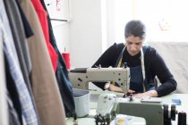 Alfaiate fêmea madura usando máquina de costura na lavanderia — Fotografia de Stock