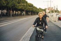 Ritratto di donna anziana sorridente con uomo che cavalca biciclette in strada — Foto stock