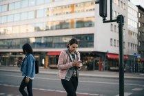 Women walking on sidewalk while using smart phones against buildings in city — Stock Photo