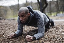 Determined male athlete performing plank position in forest — Stock Photo
