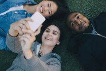High angle view of smiling woman taking selfie with friends while lying on grass — Stock Photo