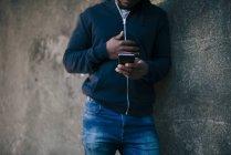 Midsection de jeune homme appuyé sur le mur tout en utilisant le téléphone intelligent — Photo de stock