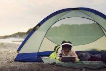 Ragazza con le cuffie utilizzando la tavoletta digitale mentre giaceva in tenda a spiaggia contro il cielo durante il tramonto — Foto stock