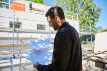 Бизнесмен читает синяки, стоя на стройке в солнечный день — стоковое фото