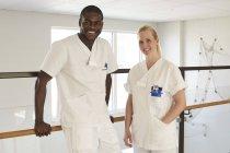 Портрет уверенно мужского и женского медсестер, стоя против перил на больничном коридоре — стоковое фото