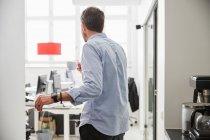 Vista panorámica del hombre de negocios que toma café mientras se encuentra en el mostrador de cocina. - foto de stock