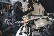 Mecânico verificar óleo com a vareta no auto oficina — Fotografia de Stock