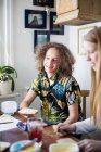 Lächelnde Freunde sitzen beim Frühstück zu Hause am Tisch — Stockfoto