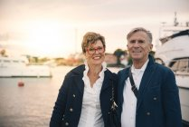 Portrait of confident senior couple smiling at harbor — Stock Photo
