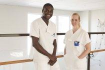 Porträt von glücklichen männlichen und weiblichen Krankenschwestern gegen Geländer im Krankenhausflur — Stockfoto