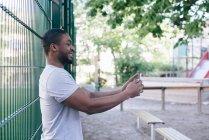Vista lateral del hombre sonriente tomando selfie mientras está de pie contra la valla - foto de stock