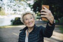 Улыбающаяся пожилая женщина делает селфи со смартфоном в парке — стоковое фото