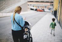Rear view of mother using mobile phone and pushing baby stroller while walking with son on sidewalk in city — Stock Photo