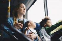 Mãe com crianças segurando telefone celular enquanto olha através da janela do ônibus — Fotografia de Stock