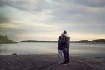 Vista posterior de la pareja abrazándose y permanente en la playa mirando lago contra el cielo durante la puesta de sol - foto de stock