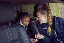 Sorrindo mulher sentada com a filha no carro — Fotografia de Stock