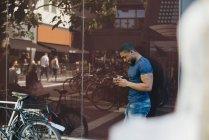 Вид збоку молодий чоловік, за допомогою мобільного телефону, поки стоїть на стіни в місті — стокове фото