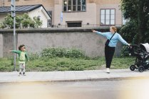 Rapaz, apontando e mostrando a mãe com carrinho de bebê em pé na calçada da cidade — Fotografia de Stock