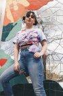 Retrato de ángulo bajo de mujer joven de pie contra la pared de mosaico - foto de stock