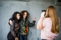 Rear view of girl photographing smiling teenage friends standing against wall at parking garage — Stock Photo