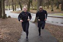 Full length of multi-ethnic couple jogging on wet street — Stock Photo