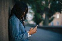 Вид збоку з використанням смартфону стоячи проти стіни дівчинки-підлітка — стокове фото
