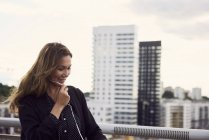 Mature woman talking through earphones at footbridge in city — Stock Photo