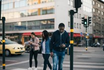 People crossing street while using smart phones against buildings in city — Stock Photo