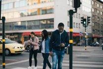Rua de passagem de pessoas durante o uso de telefones inteligentes contra edifícios na cidade — Fotografia de Stock