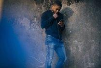 Jovem, encostado na parede enquanto estiver usando o celular — Fotografia de Stock