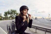 Mature businesswoman fastening helmet on street against sky — Stock Photo