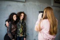 Vista posteriore della ragazza che fotografa gli amici adolescenti in piedi contro il muro nel garage — Foto stock