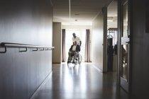 Longitud total de enfermero empujando a hombre mayor en silla de ruedas en el pasillo del hospital - foto de stock