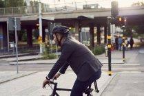Vista laterale dell'uomo d'affari in bicicletta per strada in città — Foto stock